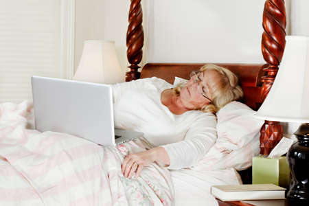 more mature: Mature woman falls asleep while trying to do a few more e-mails before bedtime