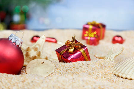 Christmas ornaments in the sand - red packages
