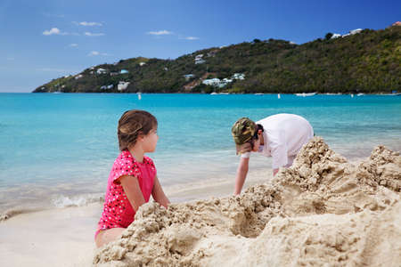 sandcastles: Brother & sister build sandcastles on the beach Stock Photo