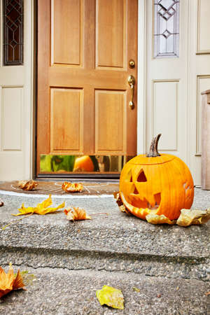 Front steps and open front door with fall leaves and jack-o-lantern Stock Photo - 9821583