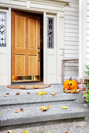 Front steps and open front door with fall leaves and jack-o-lantern photo