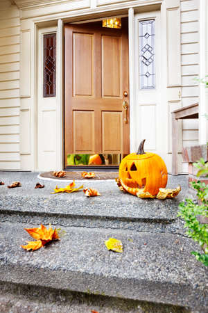 Front steps and open front door with fall leaves and jack-o-lantern Stock Photo - 9821491