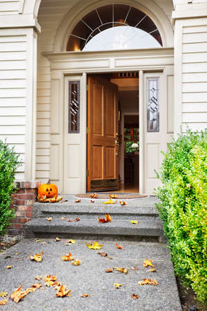 door leaf: Front path, steps and open front door with fall leaves and jack-o-lantern Stock Photo