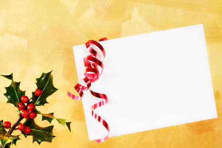 White envelope with holly and red curling ribbon over a gold hand painted background Stock Photo - 9821313