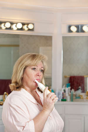 50 55: Mature womans morning routine - cleaning her teeth Stock Photo