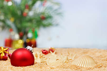 Christmas ornaments in the sand with a palm decorated for the season in the background Stock Photo