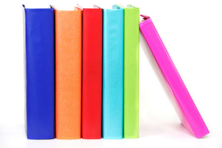 Row of colorful books propped up by one leaning on the end Stock Photo - 9821783