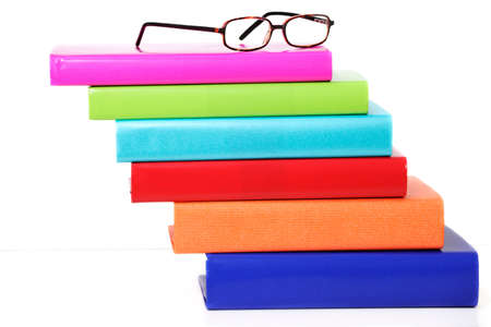 Staggered stack of colorful hardback books with horn rim reading glasses Stock Photo - 9821672
