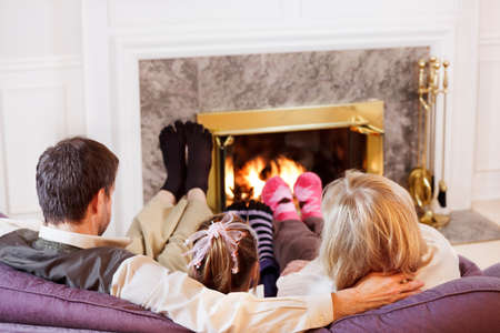 Mom, Dad and daughter warm their socked feet by the fire Stock Photo - 9821001
