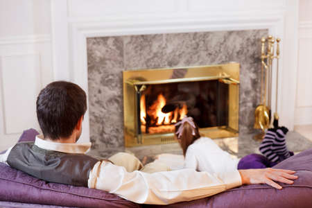 Dad sits and relaxes as his daughter reads by the fire photo