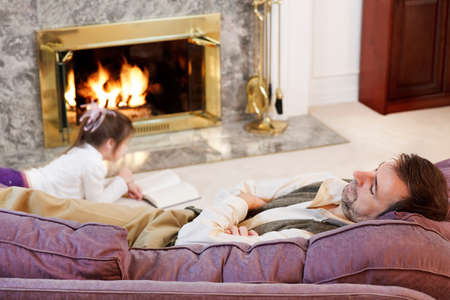 Little girl reads by the fire while Dad naps photo