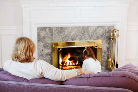 Mother sits on the sofa while her daughter reads on the floor by the fire photo
