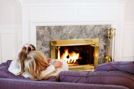 Mother and daughter cuddle by the fireside photo