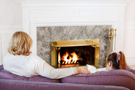 Mother and daughter sit on the sofa  to read by the fire photo