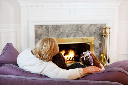 Mother hugs her son and daughter by the fireside photo