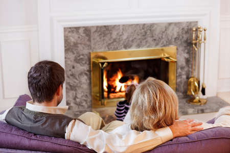 Husband & wife sit together on the sofa while their daughter reads by the fire photo