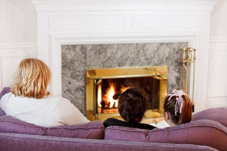 Mother son and daughter sit on the sofa  to read by the fire photo