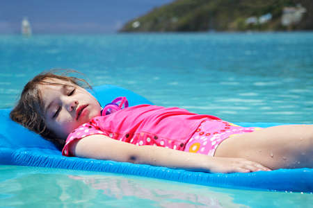 virgin girl: Young girl, eyes closed & covered in sand, floating peacefully in Magens Bay