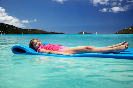 Young girl, eyes closed & covered in sand, floating peacefully in Magens Bay photo
