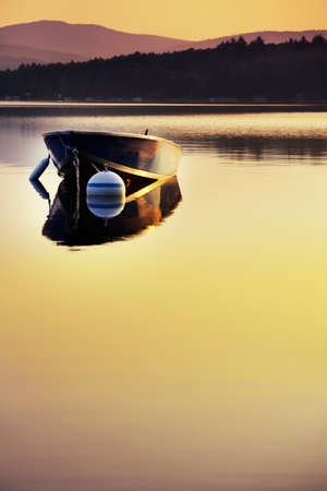 Small boat moored on a still dawn lake photo