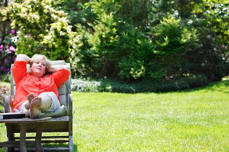 Mature woman sitting & thinking outside photo