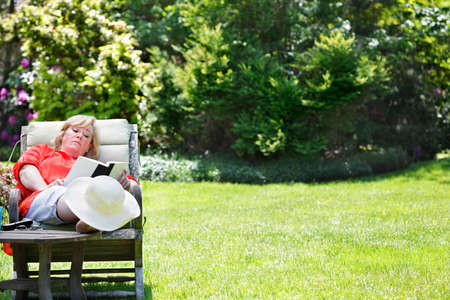Mature woman reading in a sunny garden chair photo