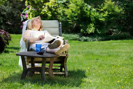 comfortable chair: Mature woman napping in a garden chair