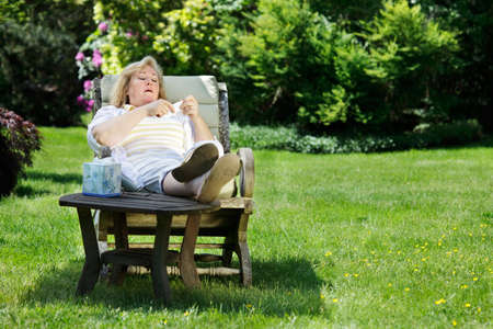 comfortable chair: Mature woman about to blow her nose