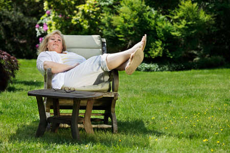 footstool: Mature woman relaxing in a sunny Spring garden Stock Photo