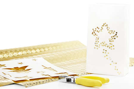 Gold paper, bag, stencils and decorative punch to make a Christmas gift bag Stock Photo - 9829915