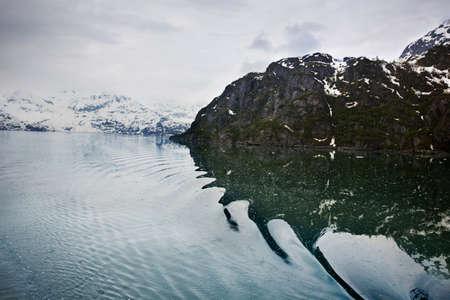 distort: Ripples distort the reflected mountains in Glacier Bay National Park, Alaska