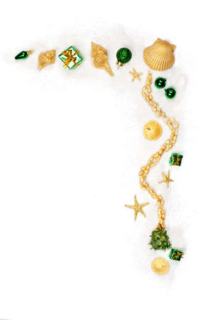 Green ornaments & shells painted gold on white sand Stock Photo - 9829910