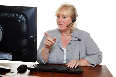 Mature customer service representative with headset points at the monitor photo