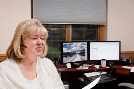 Mature woman reacts to her phone conversation in her home office photo