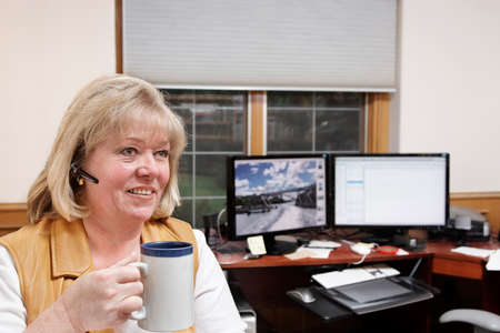 office break: Mujer madura en el tel�fono con una taza de caf�  t� en una oficina en casa