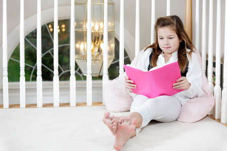 Young girl sitting on the floor reading photo