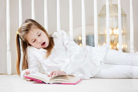 Young girl starts to yawn as shes lying on the floor reading photo