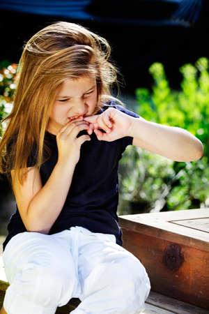 habits: Bad habits - young girl biting her nails Stock Photo