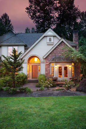 Lights shine from a suburban home at dusk photo