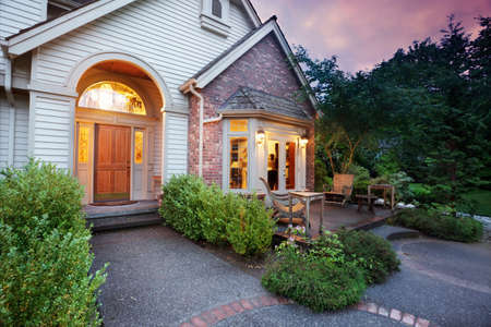 Lights shine from a suburban home at dusk