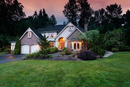 yard: Lights shine from a suburban home at dusk