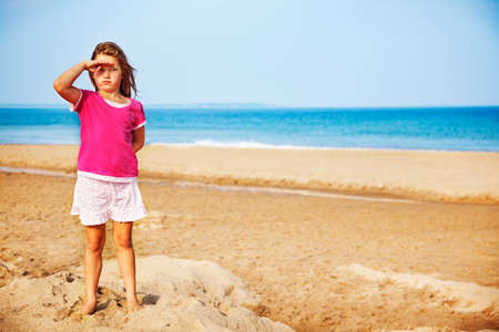 children sandcastle: Little girl salutes standing on smushed sand castle at the beach Stock Photo