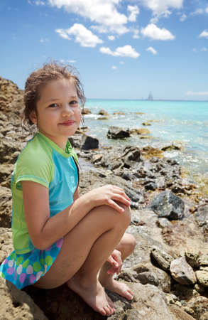 virgin girl: Young girl sitting on the rocks at waters edge