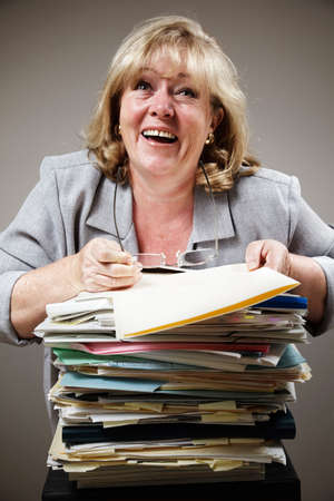 demented: Mature woman losing it in demented laughter as work piles up