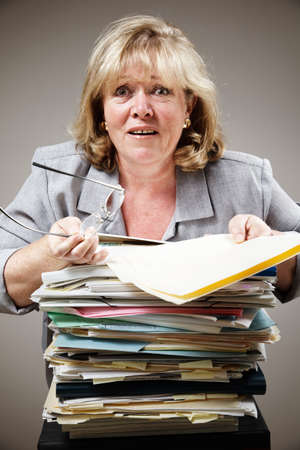 Mature woman overwhelmed by the stack of paperwork photo