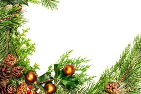 Frame of evergreen branches,  holly, pine cones and Christmas decorations