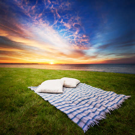 picnic blanket: Blanket and pillows for two in a peaceful spot Stock Photo