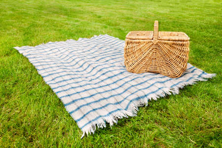 Picnic blanket and basket in the grass photo