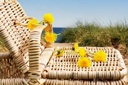Close up of wicker picnic basket lid with dandelion chain with beach in the background photo