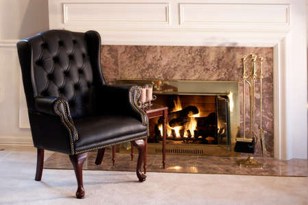 mantelpiece: Black leather chair by the fire Stock Photo